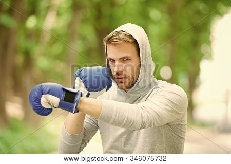 Be Strong. Man In Boxing Gloves Punching. Sport And Sportswear Fashion. Boxer Man In Hood. Ready To