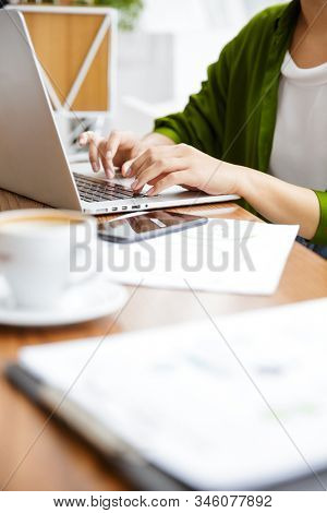 Close up of a woman working on laptop computer over cafe table indoors, drinking coffee