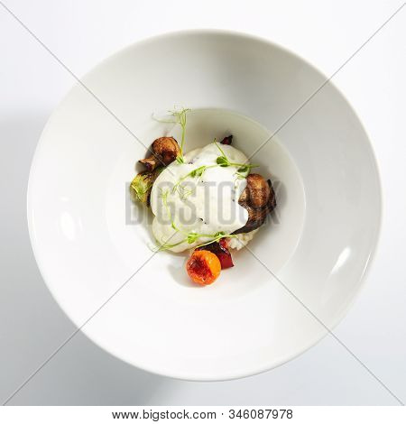 Risotto with grilled vegetables, carnaroli rice and cheese foam on white restaurant plate isolated. Traditional Italy rissoto or vegetable paella with cooked eggplants, mushrooms and greens topview