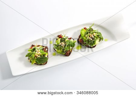Snack on whole grain bread with avocado, sun-dried tomatoes, cream cheese, pesto and pine nuts topview. Open sandwiches, thin slices of toasted black bread on white restaurant plate