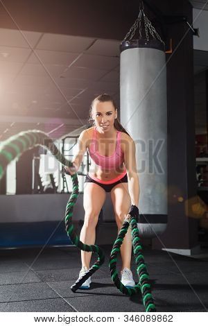 Athletic Woman Wearing Pink And Black Professional Sportswear Exercising With A Cable At The Gym. St