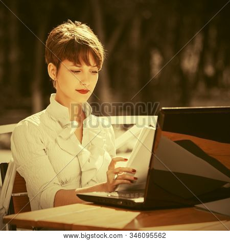 Young business woman using laptop at sidewalk cafe Stylish fashion female model in white shirt with pixie hair style