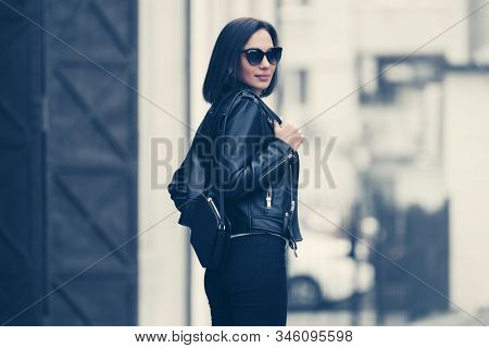 Young fashion woman with handbag walking on city street Stylish female model in black leather jacket and sunglasses