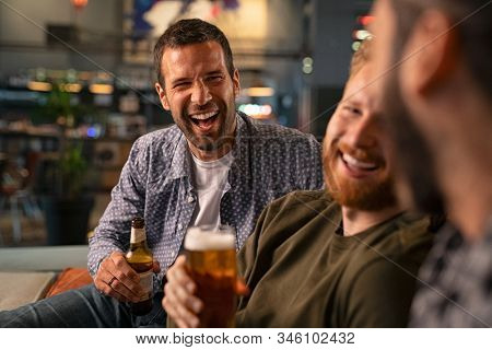 Happy young friends drinking draft beer while having fun in pub and laughing. Group of mid adult smiling men drinking beer and talk in bar while sitting on couch. guys celebrating bachelor party.