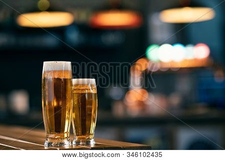 Two glasses full of beer on wooden table with copy space. A pint of draft beer and half cold pint on wooden couter at pub.