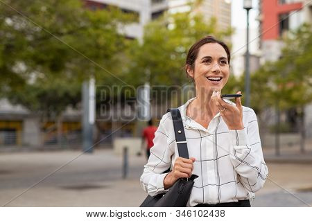 Smiling mature woman using vocal assistance over smartphone. Successful entrepreneur using mobile phone over loudspeaker on street. Happy businesswoman using cellphone for vocal message, copy space.