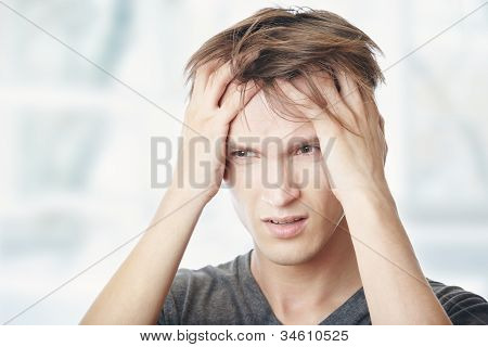 Human at home suffering from headaches. Horizontal photo poster