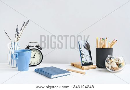 Front View Of Office Desk With Notepad, Phone, Pencils, Coffee, Clock On White Table Over White Wall