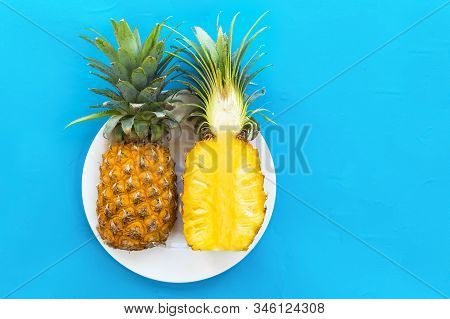 Two 2 Halves Of Ripe Yellow Pineapple On A White Plate On Blue Background. Exotic Tropical Fresh Fru