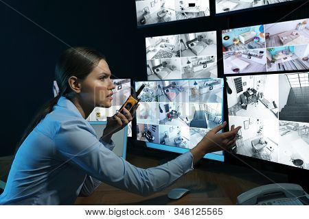 Security Guard With Portable Transmitter Monitoring Modern Cctv Cameras At Night