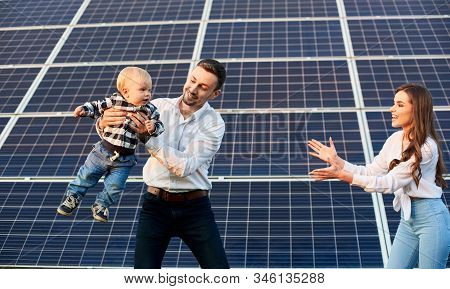 Happy Young Family With A Little Blond Child Having Fun On The Background Of Solar Panels. A Modern