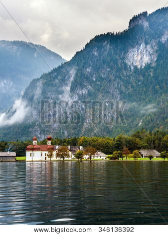 The picturesque church of St. Bartholomew with bright red domes. The cleanest lake Königssee is surrounded by high mountains. The concept of active, ecological and photo tourism
