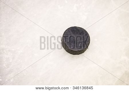 Black Ice Hocikey Rubber Puck Located On Arena Ice Rink. Ice And Puck Have Small And Deep Scratches.