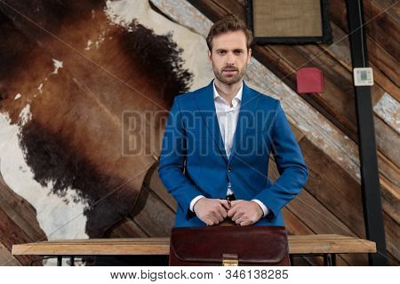 Bothered businessman holding his briefcase and looking forward, leaning on a table on coffeeshop background