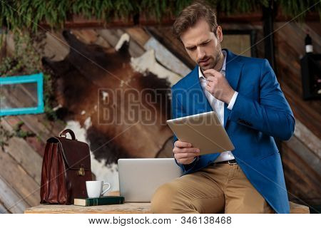 Bothered businessman reading from his tablet and frowning while leaning on a table with a laptop, briefcase, coffee cup and book on coffeeshop background