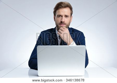 Bothered businessman biting his lips and disagreeing while holding his hand on his chin and sitting behind his laptop on gray studio background