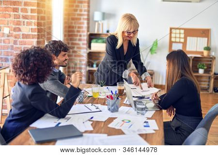 Group of business workers smiling happy and confident. Working together with smile on face. Middle age beautiful woman standing explaining documents at the office