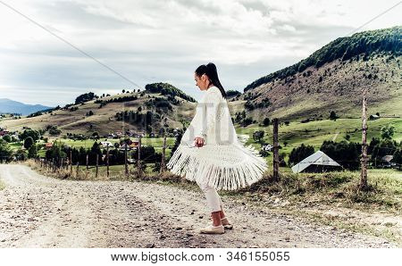 The Girl In White Walks On The Streets Of A Village In The Mountains On A Beautiful Autumn Day.the Y