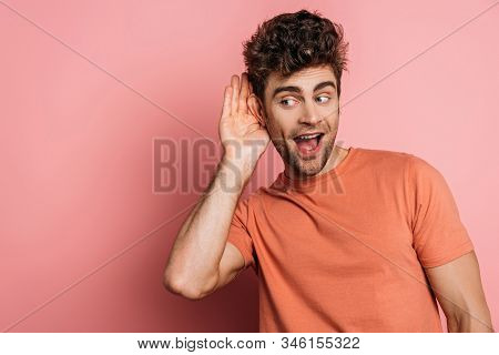 Curious Young Man Eavesdropping While Holding Hand Near Ear On Pink Background