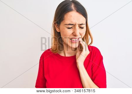 Beautiful redhead woman wearing casual red t-shirt over isolated background touching mouth with hand with painful expression because of toothache or dental illness on teeth. Dentist concept.