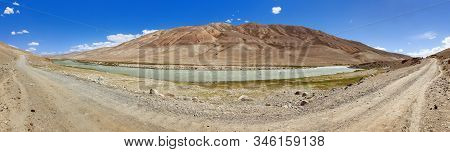 Panoramic View Of Pamir River And Pamirs Unpaved Road, Pamir Mountains On Tajikistan And Afghanistan