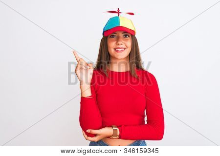 Young beautiful girl wearing fanny cap with propeller standing over isolated white background with a big smile on face, pointing with hand and finger to the side looking at the camera.