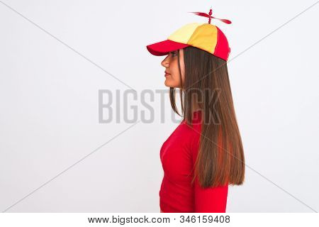 Young beautiful girl wearing fanny cap with propeller standing over isolated white background looking to side, relax profile pose with natural face with confident smile.