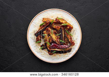 Sichuan Eggplant Stir Fry In Black Bowl At Dark Slate Background. Eggplant Stir Fry Is Chinese Cuisi