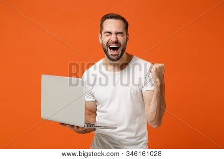 Joyful Young Man In Casual White T-shirt Posing Isolated On Orange Wall Background. People Lifestyle