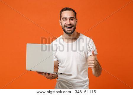 Laughing Young Man In Casual White T-shirt Posing Isolated On Bright Orange Wall Background Studio P
