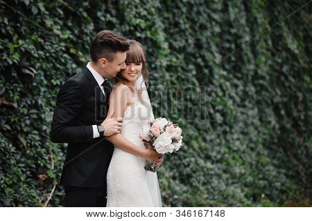 Bride And Groom At Wedding Day Walking Outdoors On Spring Green Nature. Bridal Couple, Happy Newlywe