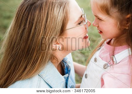 Blonde Mother With Two Cute Daughters Are Walking And Having Fun Outdoors. Stylish, Casual Clothes.