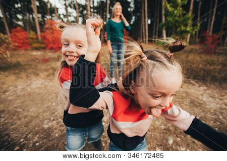Blonde Mother And Her Twin Daughters Are Walking In The Autumn Forest Among Red Trees.