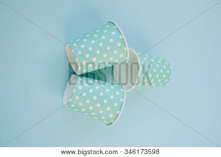 Blue Paper Cups With Polka Dots On A Blue Background.  The Concept Of Holiday Dishes, Dishes For A P