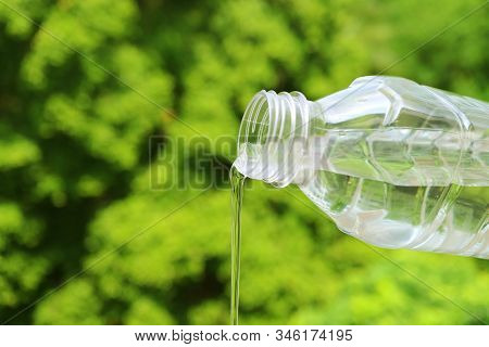 Mineral Water Flowing From Plastic Bottle With Blurry Green Foliage In Background