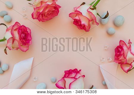 Frame From Fresh Pink Roses, Ribbon, Beads And Pebbles On Pink Background. Top View. Flat Lay. Copy