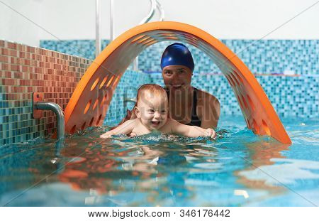 Playful Active Training In Swimming Pool. Little Cute Boy Is Learning How To Float With His Supporti