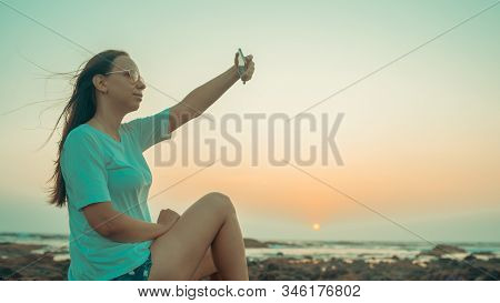 A Beautiful Young Woman Is Taking Selfie On A Mobile Phone, Sitting On The Rocks By The Sea Against