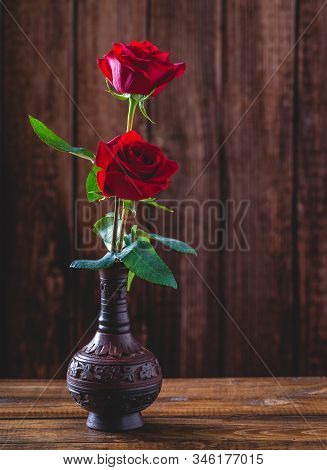 Two Red Roses In A Vase On A Wooden Surface And Background With Copy Space