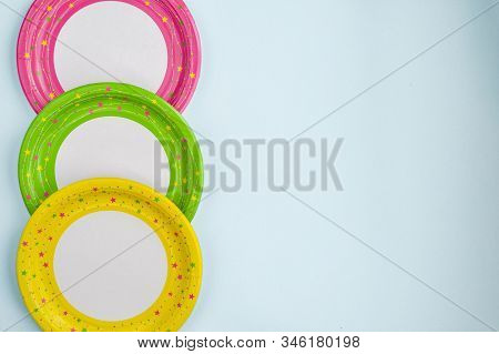 Bright Yellow, Green And Pink Paper Plates On A Blue Background. Paper Decoration With A Ribbon On A
