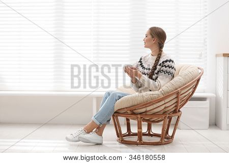 Young Woman With Hot Drink In Papasan Chair Near Window At Home
