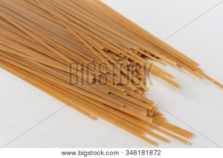 Long Flat Brown Macaroni On A White Background.