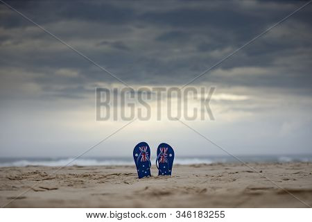 Australian Flag Thongs Sticking Upright In Sand On An Aussie Beach With Dramatic Storm Clouds Backgr