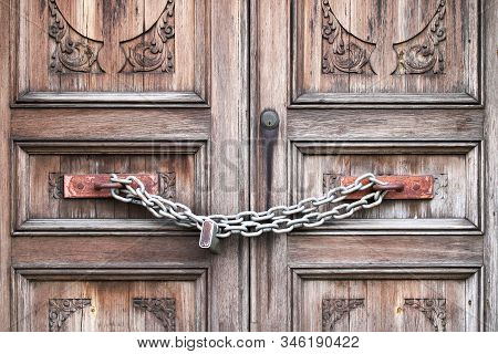 A Double Wooden Door Chained Closed. Closeup Of Old Wooden Door With Closed Padlock On A Chain. A Ch