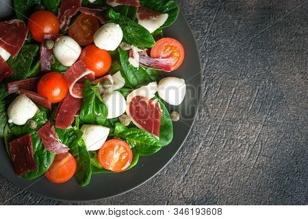 Salad With Prosciutto, Mozzarella, Fresh Vegetables On A Dark Plate On A Black Background Top View C