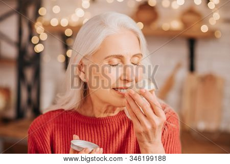 Grey-haired Beautiful Lady In Red Smelling New Cream