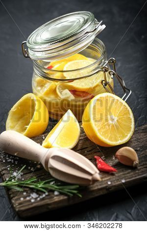 Salted Lemons In Glass Jar With Ingredients On A Dark Background. Moroccan Cuisine.