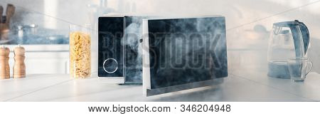 Panoramic Shot Of Broken And Steamy Microwave On Table In Kitchen