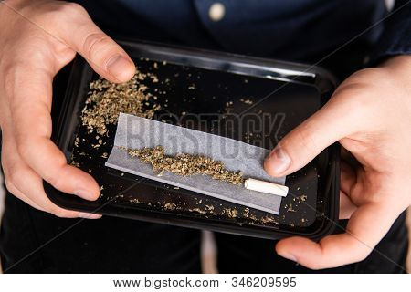 Preparing A Joint And Drug Paraphernalia Concept Theme With Close Up Man Hands Rolling A Joint With