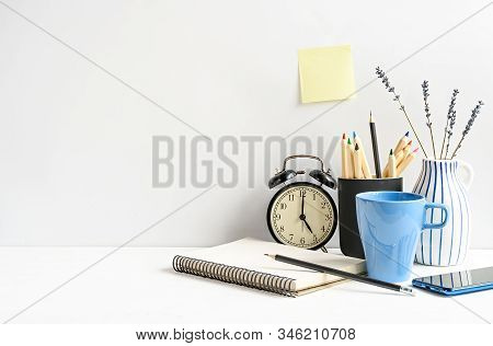 Office Desk With Notepad, Pencils, Coffee, Clock On White Table Over White Wall. Front View. Mockup